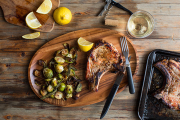 Overhead view of pork chop with brussels sprout served on plate