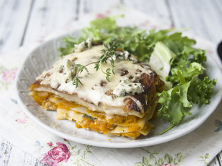 Slice of Pumpkin and Spinach Lasagne with blue cheese and salad on a White Wooden Table. Selective focus, copy space, closeup