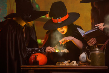 Photo of three witches in hats cooking poison in cauldron at dark room