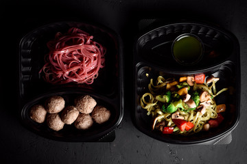 pink pasta with steamed pasta and green pasta with vegetables in eco boxes. on a black background. Healthy food delivery. Vegetarian dish. Vegetarian Delivery.