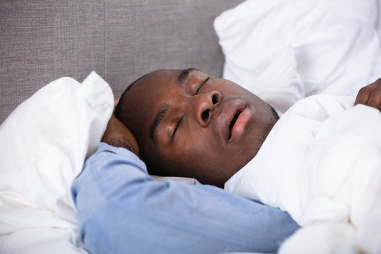 African Man Sleeping On Bed