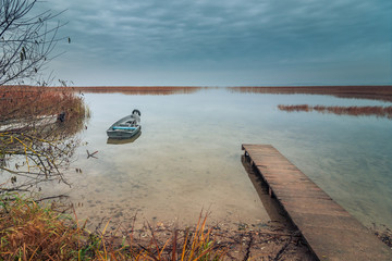 view from the coast of the lake to a beautiful water landscape with a boat, wooden pier and coastal reeds in the light of autumnal twilight