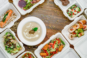 Healthy food delivery. Take away for diet. Fitness nutrition, vegetables, meat and fruits in white eco boxes. Top view, flat lay at natural wood with copy space