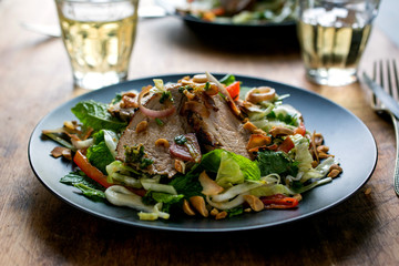 Close up of a roasted pork with salad served on plate