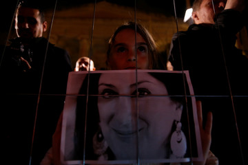 A girl holds a photo of assassinated anti-corruption journalist Daphne Caruana Galizia while looking through a fence towards the newly rebuilt makeshift memorial during a vigil, outside the Courts of Justice in Valletta