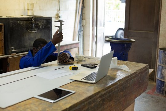 Worker using vernier caliper in foundry workshop
