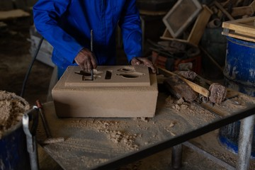 Worker making foundry molding in workshop