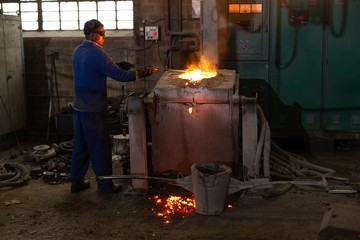 Worker molting metal in foundry workshop
