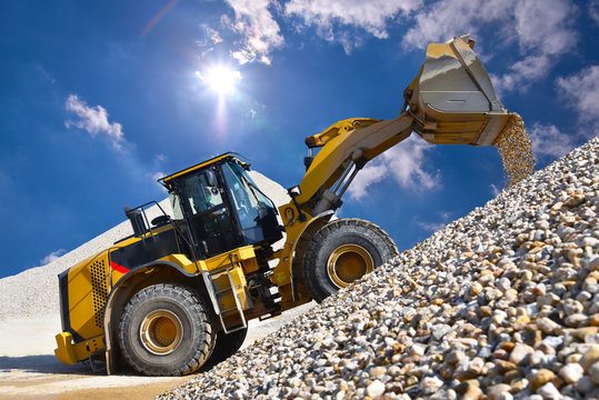 Wheel loader in a gravel pit during mining - heavy construction machine in open cast mining