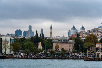 Sinan Pasha Mosque in Besiktas, Istanbul, Turkey with modern buildings at the background and crowd in the quay