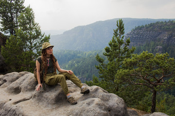 Young woman hiker travel alone in the forest and mountains with backpack