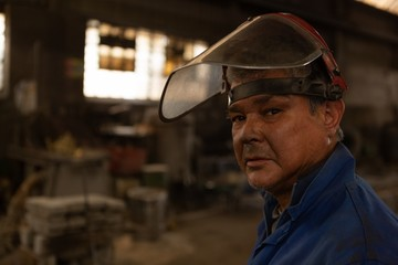 Worker looking at camera in foundry workshop