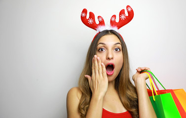 Suprised christmas woman with reindeer horns and shopping bags looking at the camera shocked on white background. Copy space.