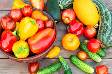 Vegetables: tomatoes, cucumbers, paprika, pepper, zucchini in a clay bowl and on a wooden table. Ingredients for the preparation of summer vegetable salad