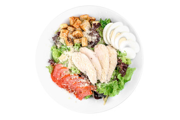 Caesar salad with chicken fillet, iceberg salad, egg, cherry tomato, white toast and parmesan cheese in a white plate isolated on white background. top view. flat lay