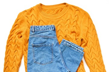 Flat lay winter outfit. Stylish yellow woolen sweater with knitted pattern and light blue high waisted jeans