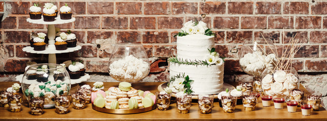 Wedding catering, table with modern desserts and cupcakes.