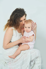 beautiful young mother with a baby in her arms is standing The concept of a happy family, motherhood