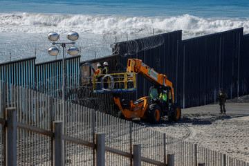 Workers on the U.S. side install concertina wire along the border fence between Mexico and the United States at Border State Park in San Diego, California