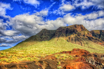 Clouds in blue sky and green fields with mountains on sunny day, north-west coast of Tenerife near Punto Teno Lighthouse, Canaria