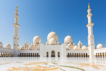 Sheikh Zayed Mosque - Abu Dhabi, United Arab Emirates. Beautiful white Grand Mosque courtyard with unique marble floor and minarets in each corner.