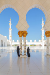 Foto op Aluminium Abu Dhabi 2 (two) tourist women wearing traditional black Abaya clothing admiring the beauty of Sheikh Zayed Grand Mosque in Abu Dhabi, United Arab Emirates.