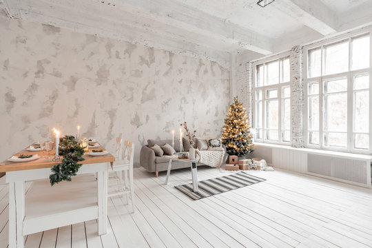 Loft style Apartment, large spacious living room with dining table and kitchen. Room with Christmas tree. Comfortable sofa, high large Windows. Light white brick wall.