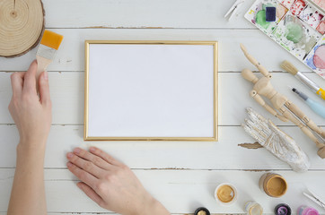 Gold photo frame mock up with woman artist hands. Space for text, art work, lettering. Flat lay, top view. Cosy, soft ,minimal.
