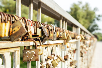 Many old rusty metal locks closed on fence of bridge over river. Love forever through time concept