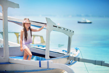 Girl child on a sail boat has a vacation on a ocean