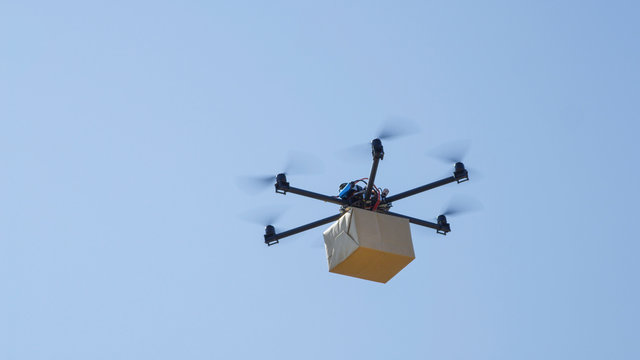 CLOSE UP: Drone delivery, multirotor helicopter flying big brown post package
