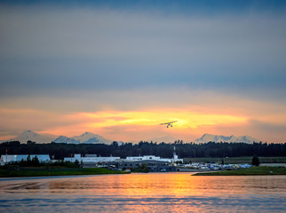 Sunset Over a Lake in Anchorage Alaska with a Float Airplane Taking off in the Distance