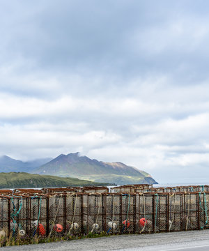 Crab Traps and Buoys Stacked on a Dock in Dutch Harbor Unalaska with Mountains in the Background