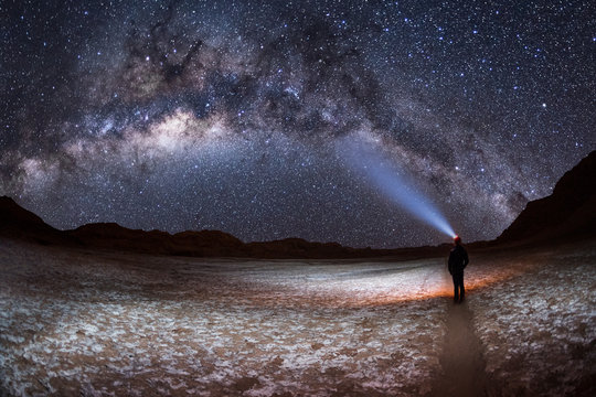 A person at night,  shining a light on the Milky Way Galaxy in the Valley of the Moon or Valle de la Luna in San Pedro de Atacama, Chile.