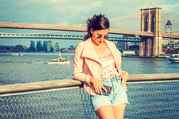 Young American Woman traveling in New York, wearing pink leather jacket, blue Denim shorts, sunglasses, standing by river, looking down, thinking. Brooklyn, Manhattan bridges, boats on background..