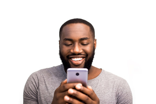 African American black user holding mobile smart phone near face, looking new app in online store. Customer service and services package. Offline and online communication. Smile, happy mood