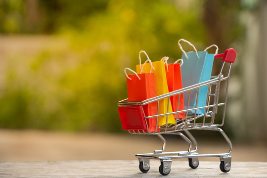 Colorful paper shopping bags in a trolley or shopping cart,E-commerce concept.