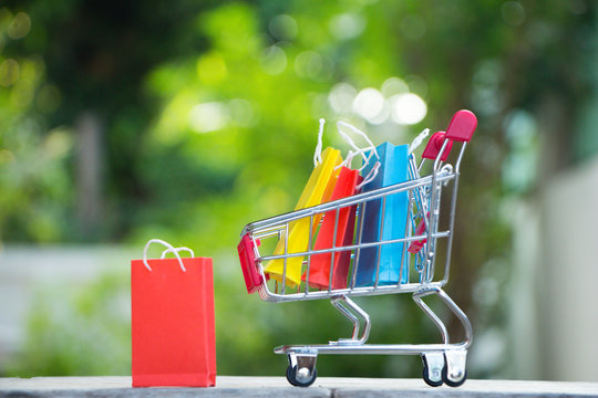Colorful paper shopping bags in a trolley,E-commerce concept.