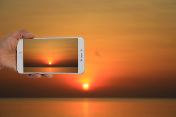 Tourist taking a picture of blur image of sunrise on the sea in morning