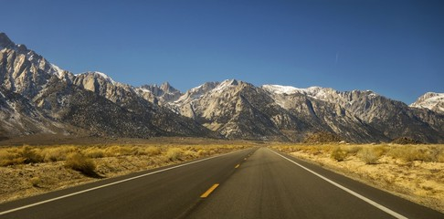 Driving Iconic California State Highway 395 in Owens Valley on Eastern Flanks of Sierra Nevada Mountains with Distant Mount Whitney on Horizon