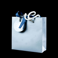 Beautiful light blue gift bag. Close up. Isolated on black background