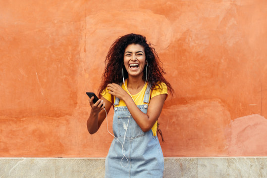 Black woman laughing and listening to music with earphones.