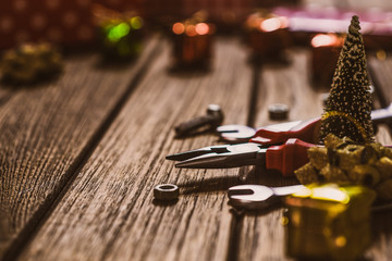 Handy Tools Christmas background concept.  Pliers and wrenches with Christmas ornament decoration on a rustic wooden table.