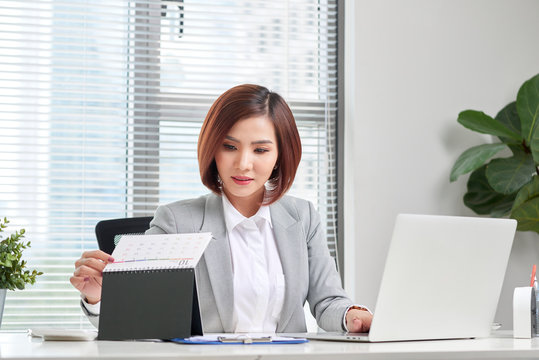 attractive businesswoman is sitting at desk with computer and calendar in the office