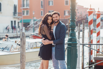 Love - romantic couple in Venice on pier. Young couple on travel vacation holidays hugging embracing each other looking at camera near canal with gondolas boats on summer sunny day, Venice, Italy