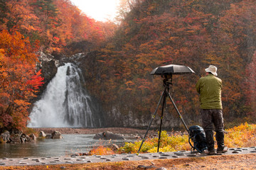 Male photographer Raining to photograph waterfall in leaves change color. In Akita, Japan