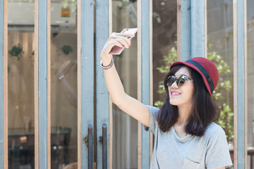 young hipster woman making selfie by her smart phone, urban life concept. .