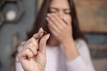 frustrated young woman holding ring in hand, crying