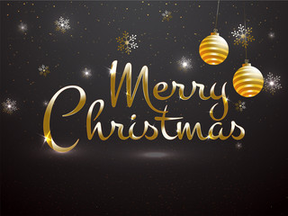 Glossy text Merry Christmas with golden baubles and snowflake decorated on black background can be used as greeting card design.
