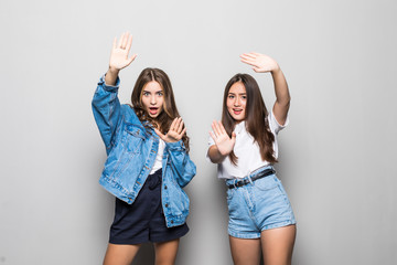 Two beautiful young girl with serious faces and gesture of hands on a gray background